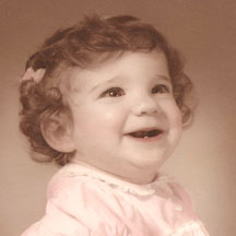 Toddler Lisa L smiles with a single tooth.