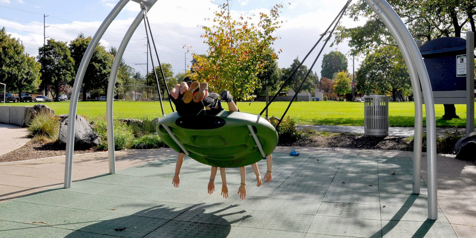 Three children enjoying an accessible multi-person swing.